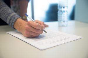 Bilde av hånden til psykolog som signerer et dokument